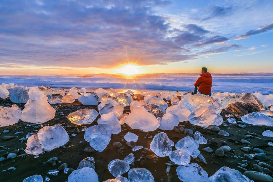 Man sitting on tiny iceberg rocks at diamond beach